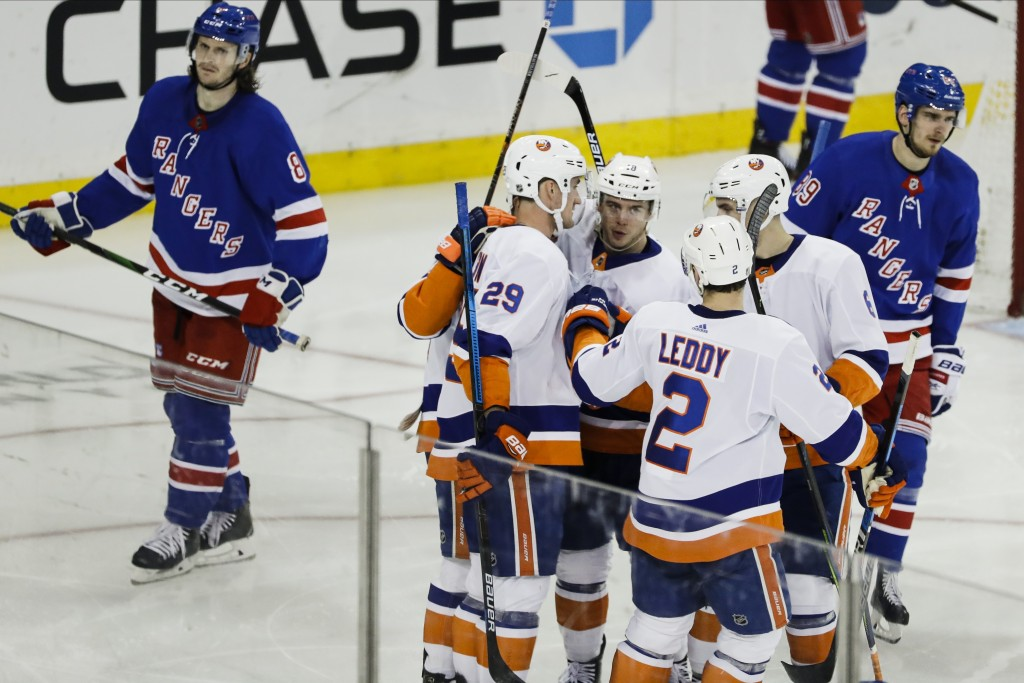 New York Islanders' Brock Nelson (29) celebrates with teammates after scoring a goal as New York Rangers' Jacob Trouba (8) and Pavel Buchnevich (89) r...