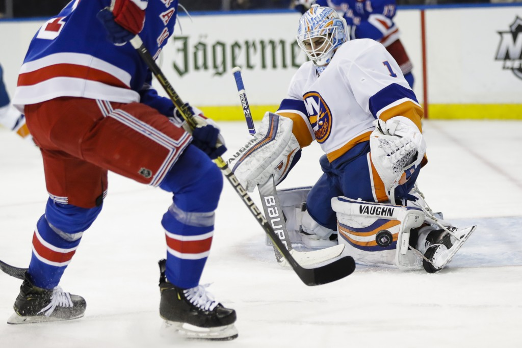 New York Islanders goaltender Thomas Greiss stops a shot on goal by New York Rangers' Brett Howden, left, during the second period of an NHL hockey ga...