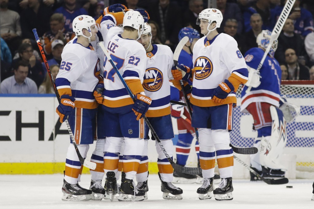 New York Islanders' Anders Lee (27) celebrates with teammates after scoring a goal during the second period of an NHL hockey game against the New York...