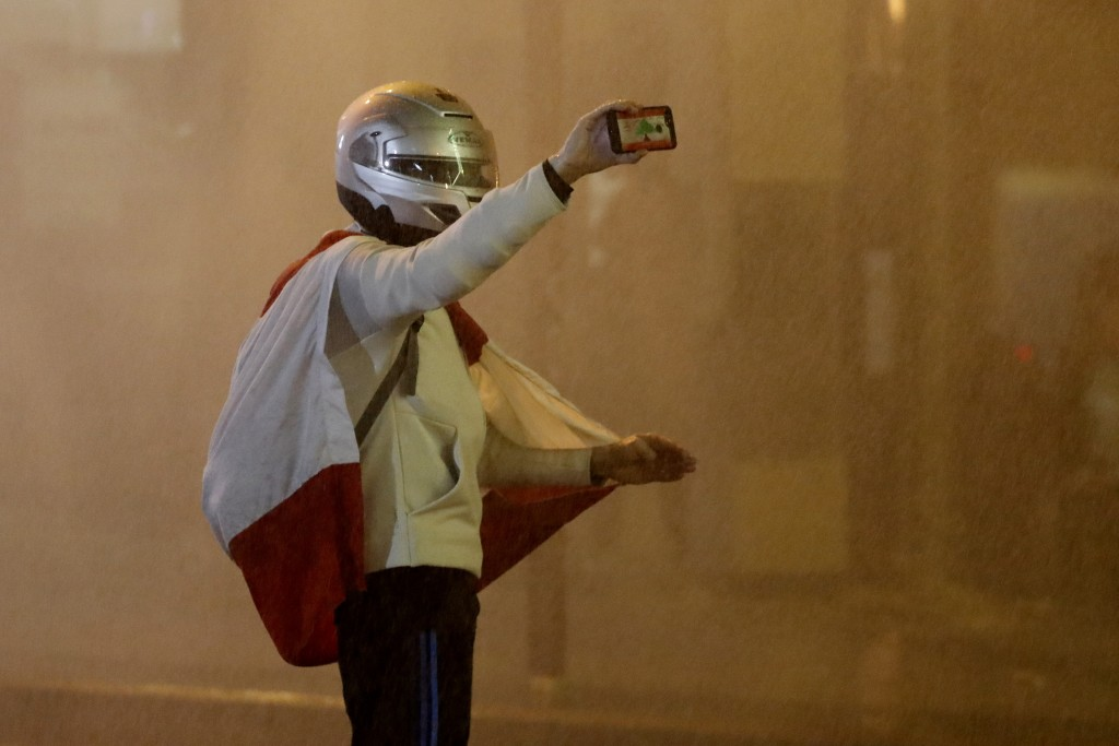 An anti-government protester is sprayed by a water cannon as he films by his mobile phone during a protest against the new government, near the parlia...