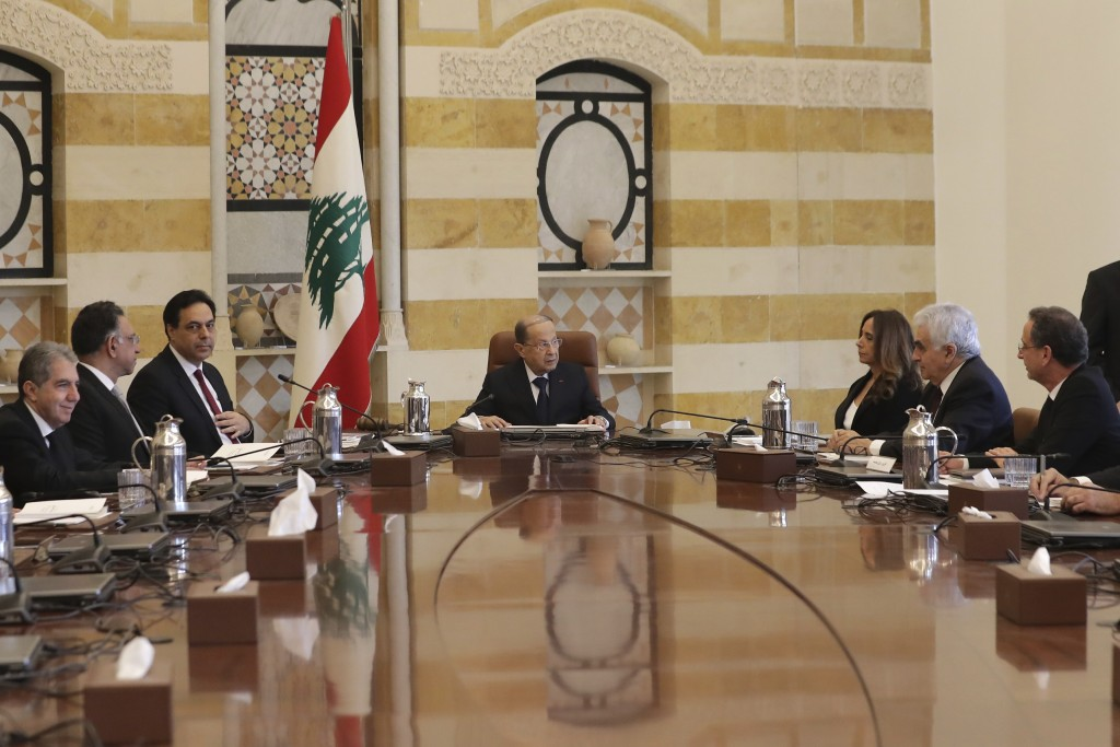 President Michel Aoun, center, speaks with Deputy Prime Minister and Minister of Defense Zeina Akr, center, right as Prime Minister Hassan Diab, cente...