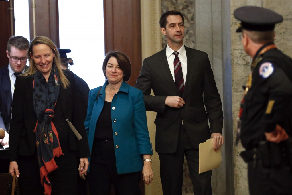 Sen. Amy Klobuchar, D-Minn., third from left, and Sen. Tom Cotton, R-Ark. forth from left, arrive at the Capitol in Washington, Tuesday, Jan. 21, 2020...