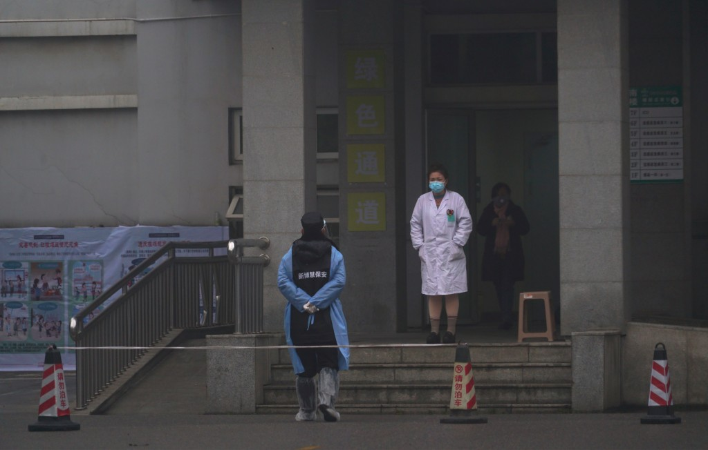 Hospital staff stand outside the emergency entrance of Wuhan Medical Treatment Center, where some infected with a new virus are being treated, in Wuha...
