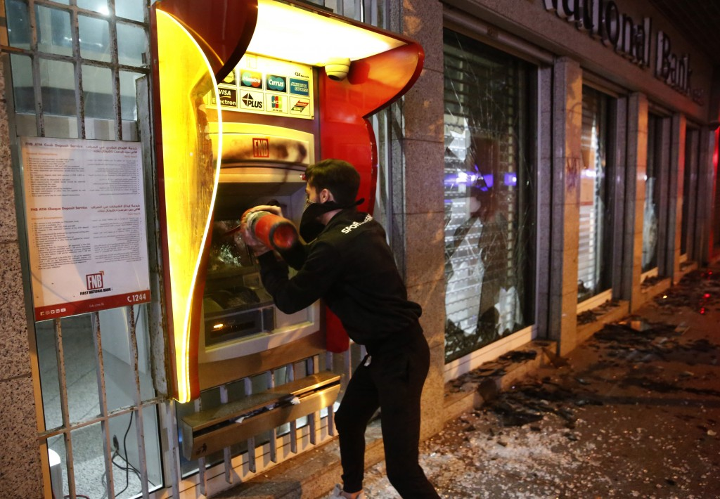 FILE - In this Tuesday, Jan. 14, 2020 file photo, an anti-government protester destroys an ATM machine during ongoing protests against the Lebanese ce...