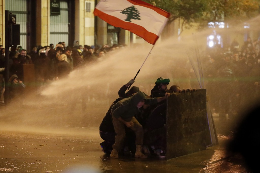 Anti-government protesters wave a Lebanese flag and hide behind a wood barrier from a water cannon as they clash with the riot police during a protest...