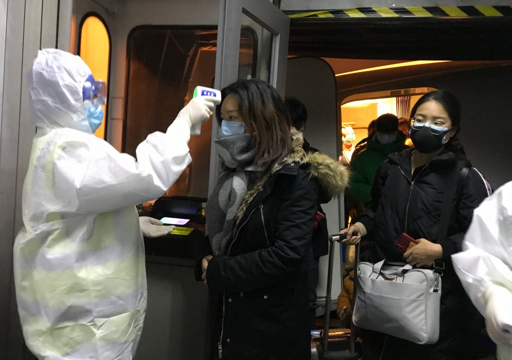 Health Officials in hazmat suits check body temperatures of passengers arriving from the city of Wuhan Wednesday, Jan. 22, 2020, at the airport in Bei...
