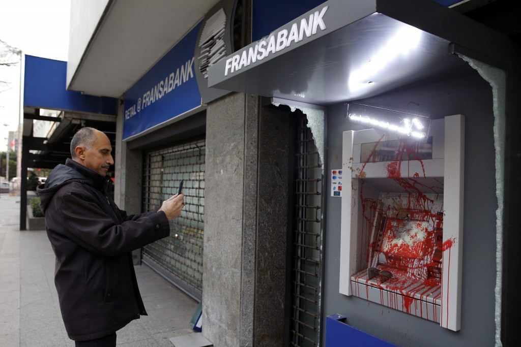 FILE - In this Wednesday, Jan. 15, 2020 file photo, a man uses his phone to take a picture of ATM screen of Fransa Bank that was painted and damaged b...