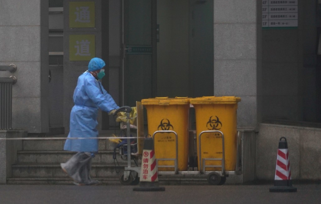 Staff move bio-waste containers past the entrance of the Wuhan Medical Treatment Center, where some infected with a new virus are being treated, in Wu...