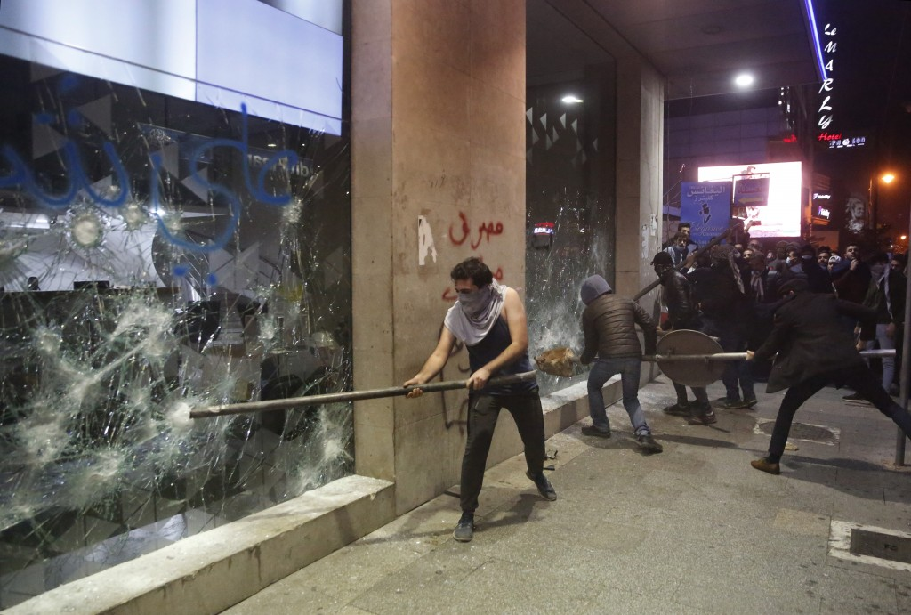 FILE - In this Tuesday, Jan. 14, 2020 file photo, anti-government protesters smash a bank widows, during ongoing protests against the Lebanese central...