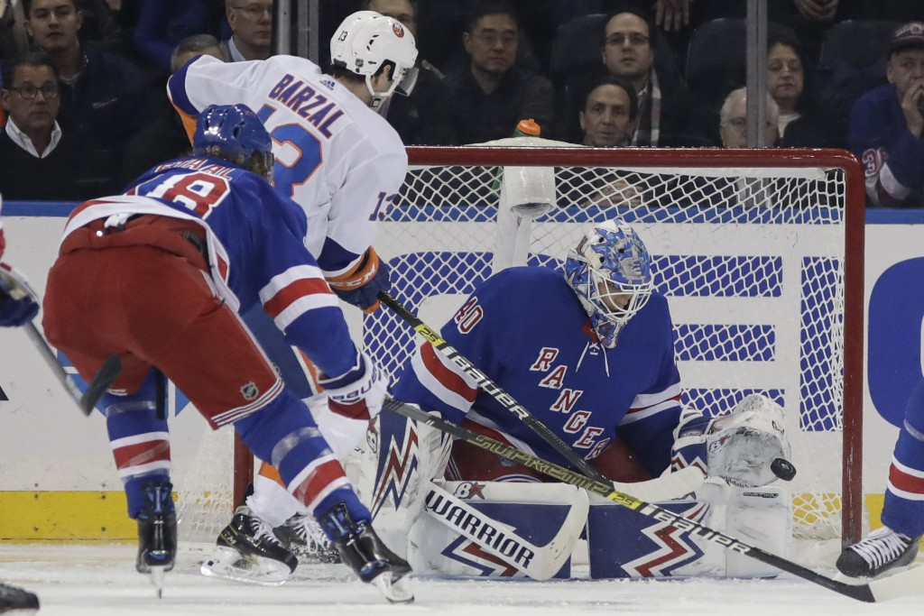 New York Rangers goaltender Alexandar Georgiev, right, stops a shot on goal by New York Islanders' Mathew Barzal during the second period of an NHL ho...
