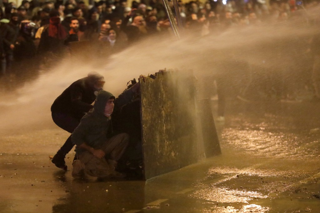Anti-government protesters hide behind a wood barrier from a water cannon as they clash with the riot police during a protest against the new governme...