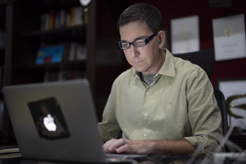FILE - In this July 10, 2019 file photo, U.S. journalist Glenn Greenwald checks his news website at his home in Rio de Janeiro, Brazil. A judge in Bra...