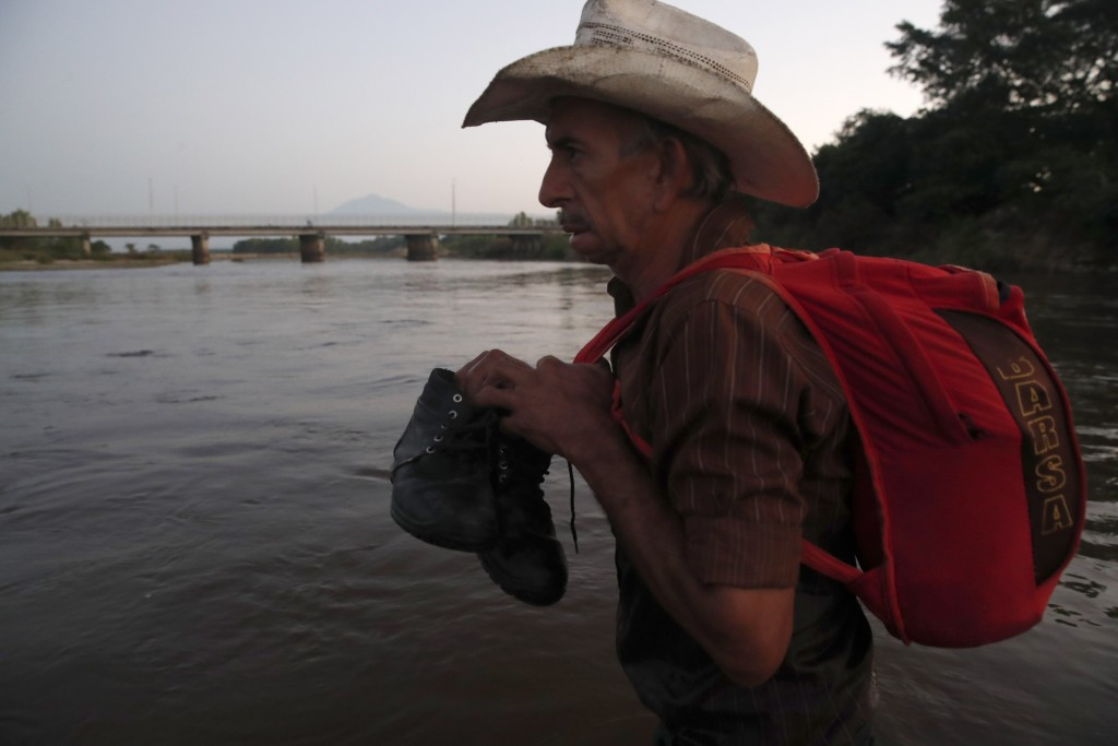 A Central American migrant crosses the Suchiate River from Tecun Uman, Guatemala, to Mexico, Thursday, Jan. 23, 2020. Migrants hoping to reach the Uni...