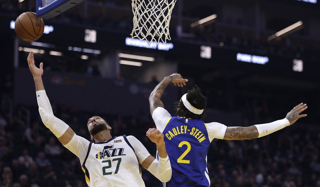 Utah Jazz center Rudy Gobert, left, reaches for a rebound past Golden State Warriors' Willie Cauley-Stein (2) in the first half of an NBA basketball g...