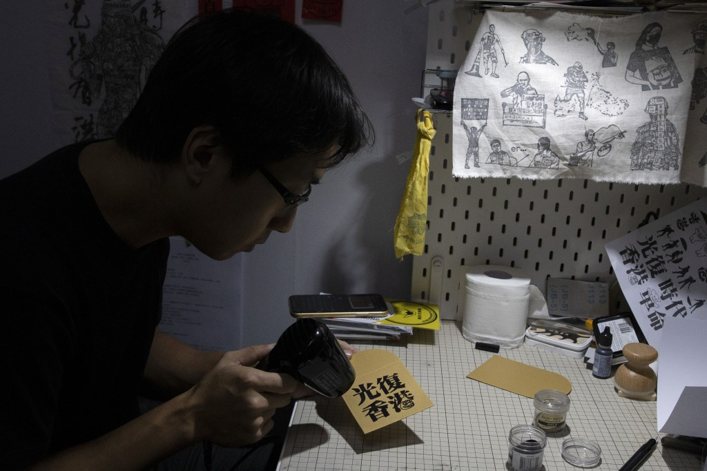 "In this Saturday, Jan. 18, 2020, photo, Jason Kwan makes a red packet with the words ""Liberate Hong Kong"" in his workshop in Hong Kong. Sharing red pa..."