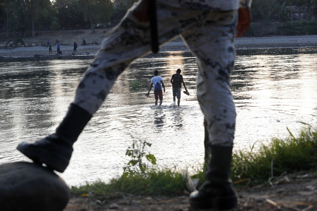 Honduran migrants who tried to enter Mexico on foot return to the Guatemalan side of the Suchiate River under the watch of a Mexican National Guard ne...