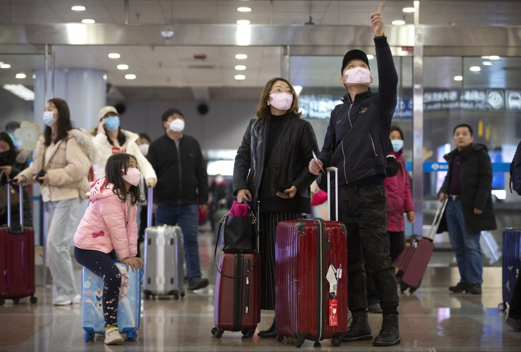 Travelers wear face masks as they stand in the arrivals area at Beijing Capital International Airport in Beijing, Thursday, Jan. 23, 2020. China close...