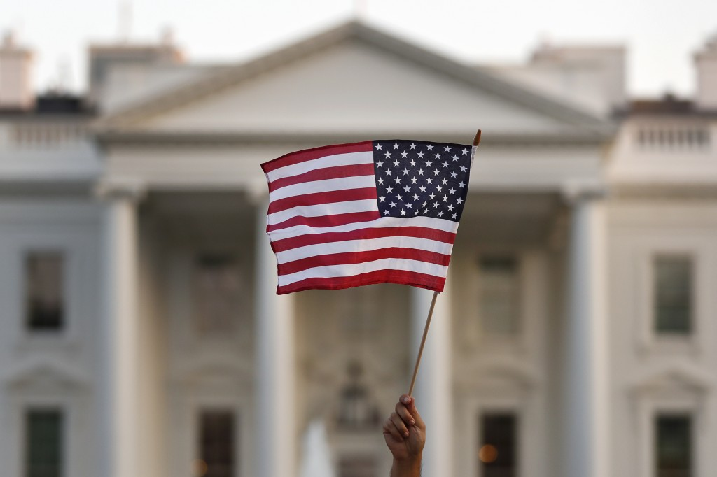 FILE - In this Sept. 2017 file photo, a flag is waved outside the White House, in Washington. The Trump administration is coming out with new visa res...
