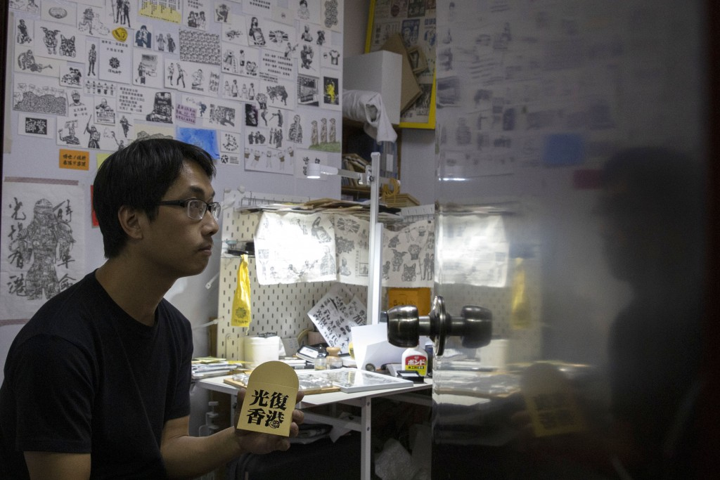"In this Saturday, Jan. 18, 2020, photo, Jason Kwan holds up a red packet with the words ""Liberate Hong Kong"" as he poses for a photo in his workshop i..."