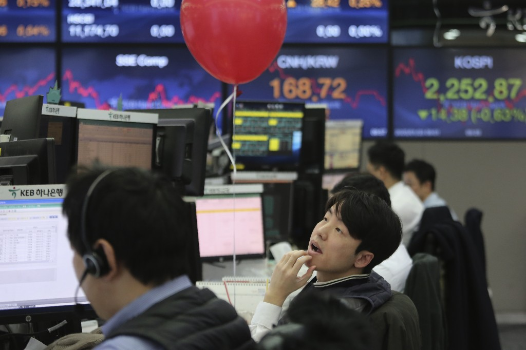 A currency trader watches monitors at the foreign exchange dealing room of the KEB Hana Bank headquarters in Seoul, South Korea, Thursday, Jan. 23, 20...