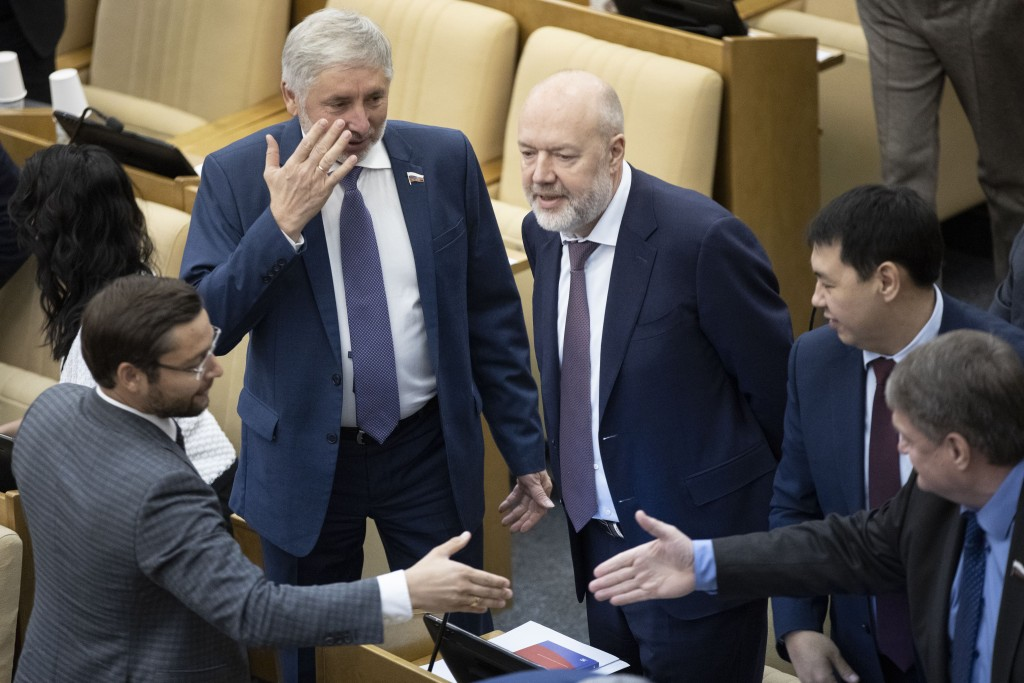 Pavel Krasheninnikov, lawmaker and co-chair of the constitutional reform working group, center, talks to his colleagues prior to a session at the Russ...