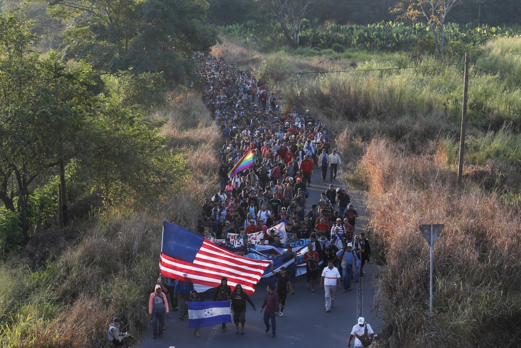 Central American migrants walk carrying a handmade U.S. flag and banners, after crossing the Suchiate River from Guatemala in Ciudad Hidalgo, Mexico, ...