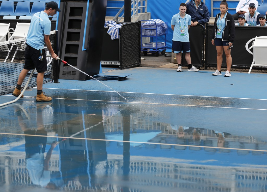 Ground staff wash red dust tainted water from an outside court as rain delayed play at the Australian Open tennis championship in Melbourne, Australia...