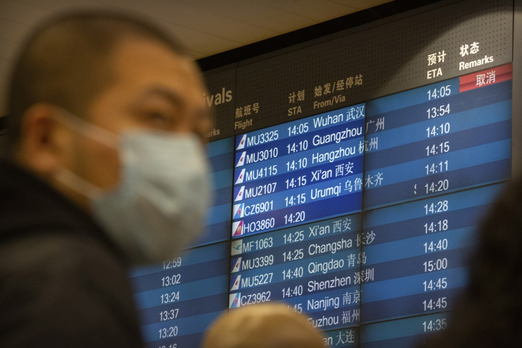 A display board shows a canceled flight arrival from Wuhan at Beijing Capital International Airport in Beijing, Thursday, Jan. 23, 2020. China closed ...