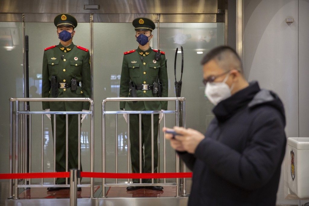 FILE - In this Thursday, Jan. 23, 2020, file photo, Chinese paramilitary police wear face masks as they stand guard at Beijing Capital International A...