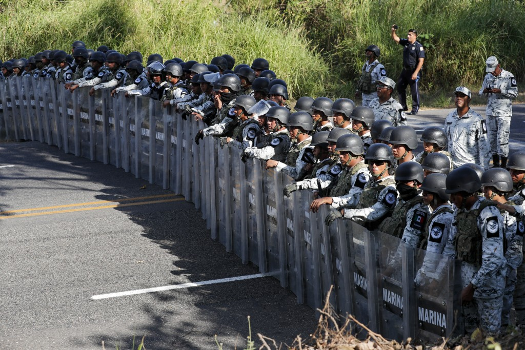 Mexican National Guardsmen block the passage of migrants on the highway leading to Tapachula, Mexico, Thursday, Jan. 23, 2020. Hundreds of Central Ame...