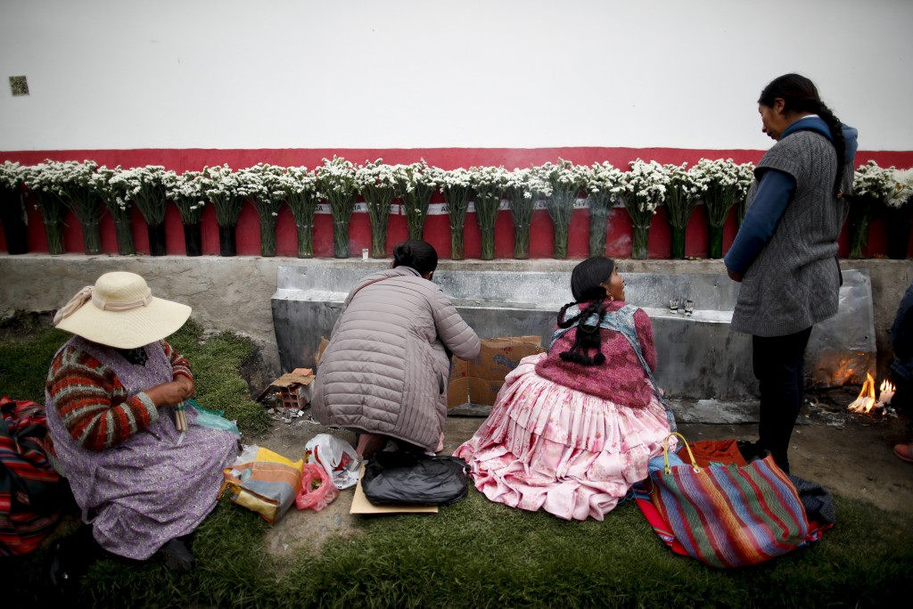 In this picture taken Jan. 7, 2020, women sit at the edge of a cemetery in La Paz, Bolivia, paying homage to unidentified deceased loved ones, who the...