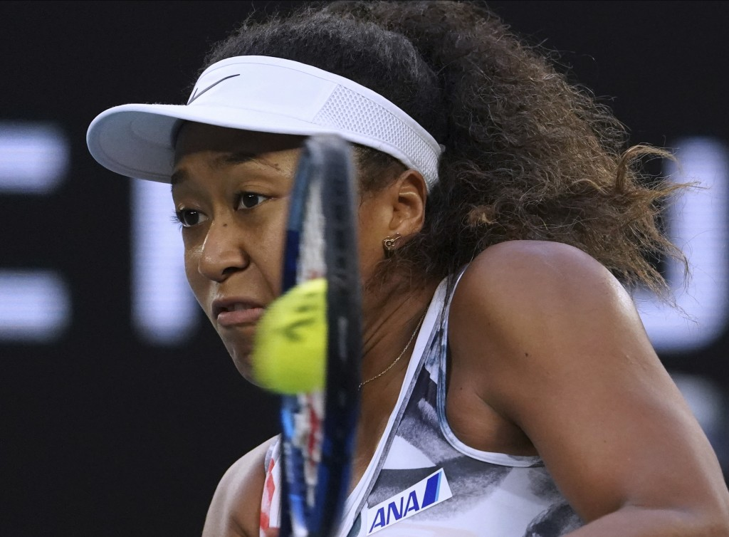 Japan's Naomi Osaka makes a backhand return to Coco Gauff of the U.S. during their third round singles match at the Australian Open tennis championshi...