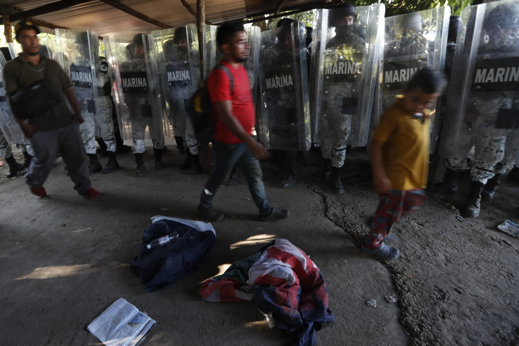 Mexican National Guards stand by as detained migrants walk past, near Tapachula, Mexico, Thursday Jan. 23, 2020. Hundreds of Central American migrants...