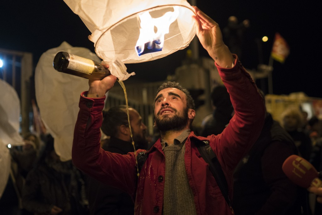 A demonstrator releases a sky lantern during a blockade of the Marseille port in southern France, Thursday, Jan. 23, 2020. Protesters marched in Paris...