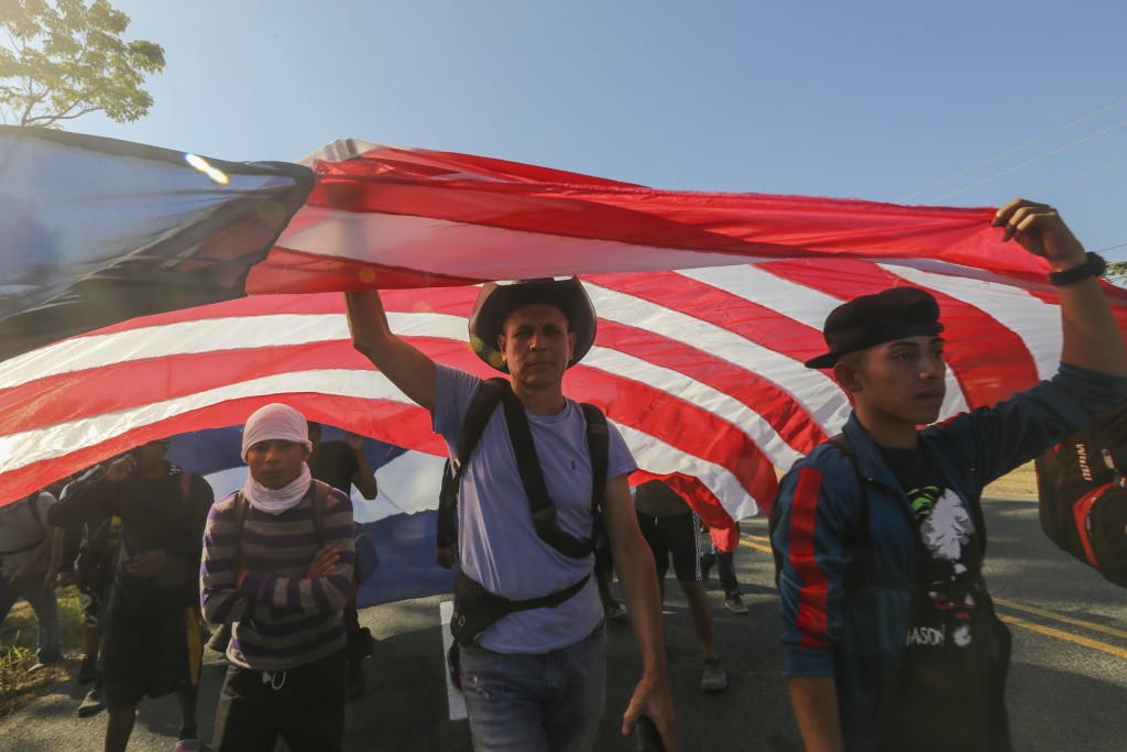 Central American migrants carrying a homemade U.S. flag walk in Ciudad Hidalgo, Mexico, Thursday, Jan. 23, 2020. Hundreds of migrants hoping to reach ...