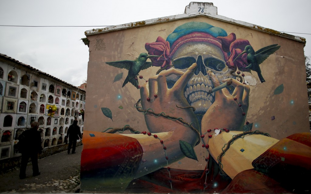 In this picture taken Jan. 7, 2020, visitors pass near a painting showing a skull at a cemetery in La Paz, Bolivia. The skulls represent the forgotten...