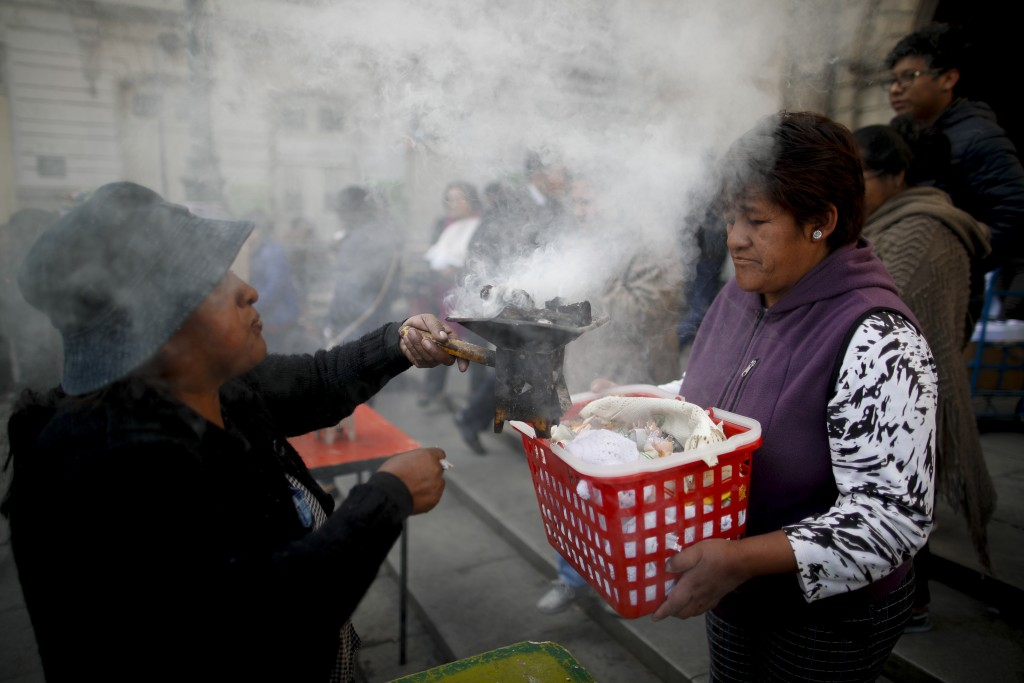 In this picture taken Monday, Jan. 6, 2020, spiritual indigenous guide Josefa Oblitas blesses a woman's baby Jesus doll outside the San Francisco Chur...