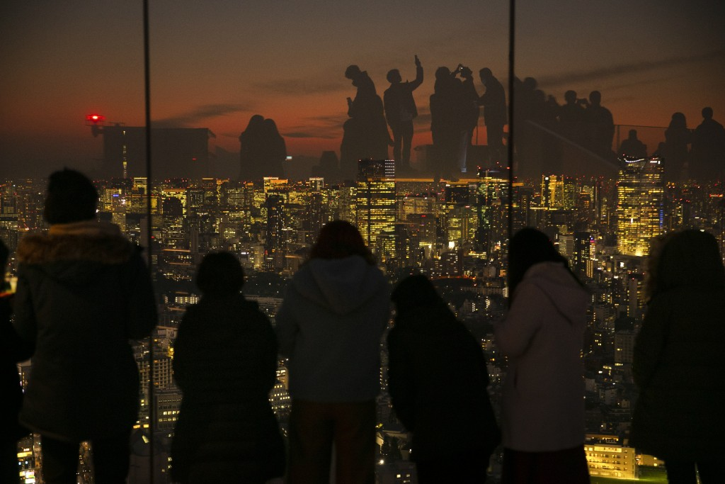 In this Monday, Jan. 20, 2020, file photo, silhouetted against sunset, visitors are reflected on the glass walls of Shibuya Sky observation deck in To...