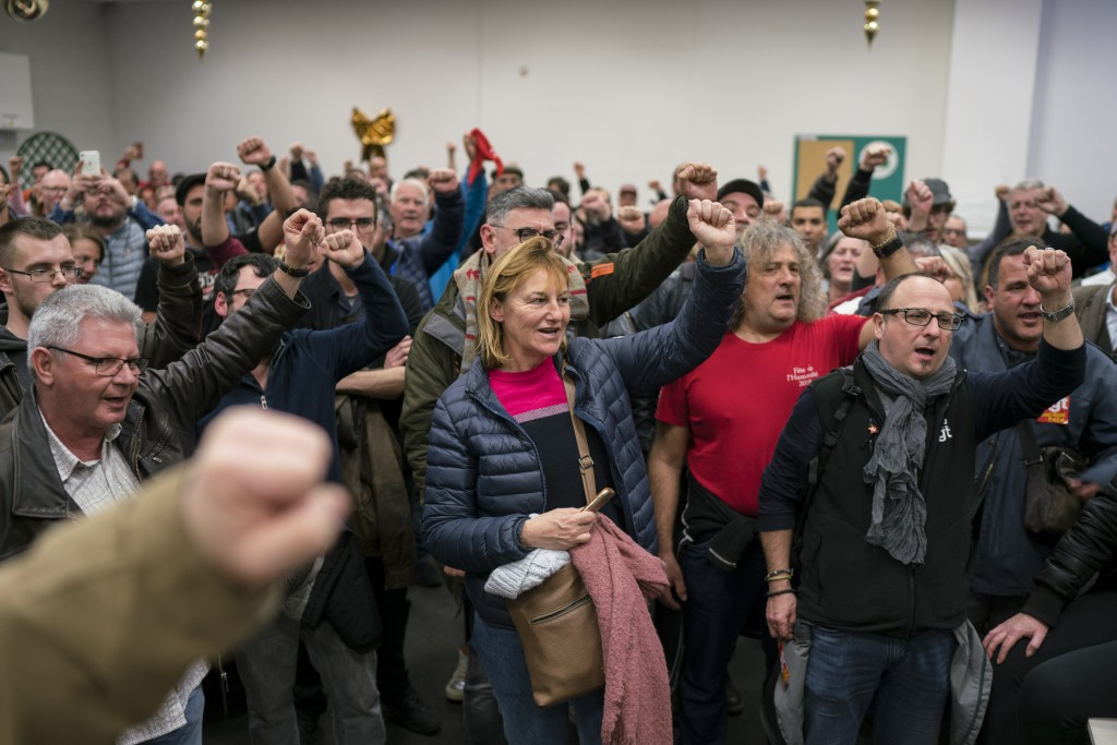 Striking dock workers gesture, during a union assembly at the Marseille port in southern France, Thursday, Jan. 23, 2020. Protesters marched in Paris ...
