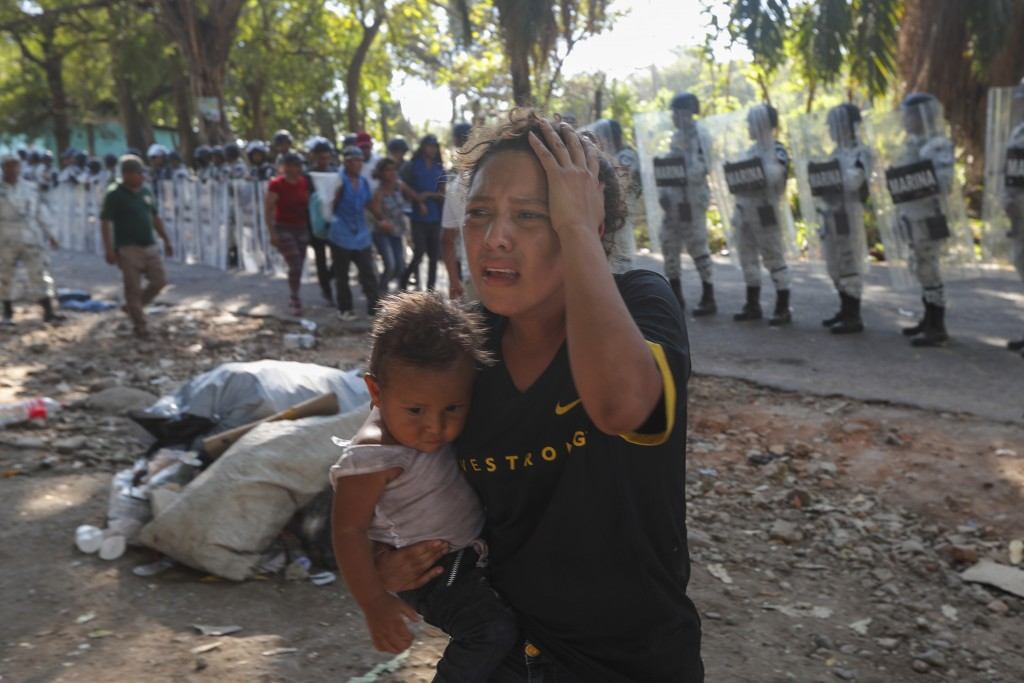 A female migrant carrying a child moves away from Mexican National Guards blocking the passage of a group of Central American migrants near Tapachula,...
