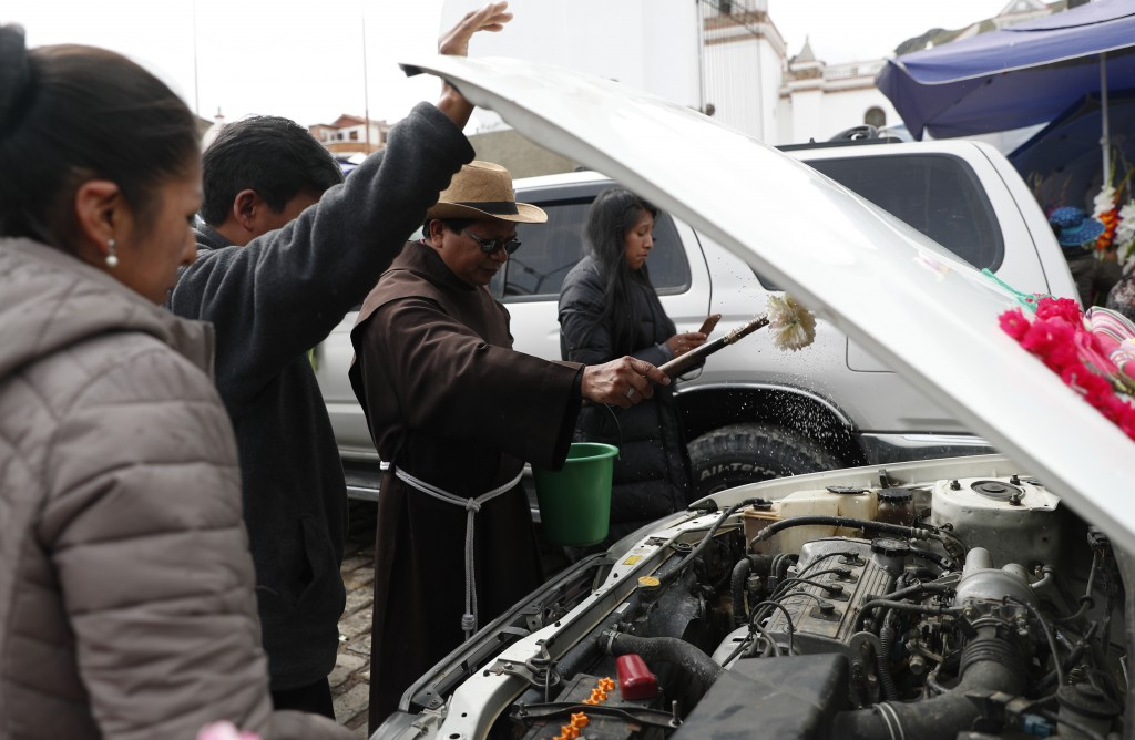 In this Jan. 11, 2020 photo, A Catholic priest blesses a car during the traditional blessing of vehicles in front of the Basilica of Our Lady Virgen i...