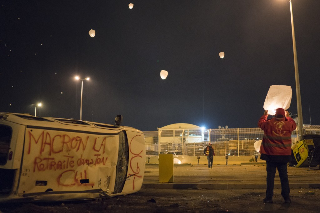 Demonstrators release sky lanterns during a blockade of the Marseille port in southern France, Thursday, Jan. 23, 2020. Protesters marched in Paris ag...