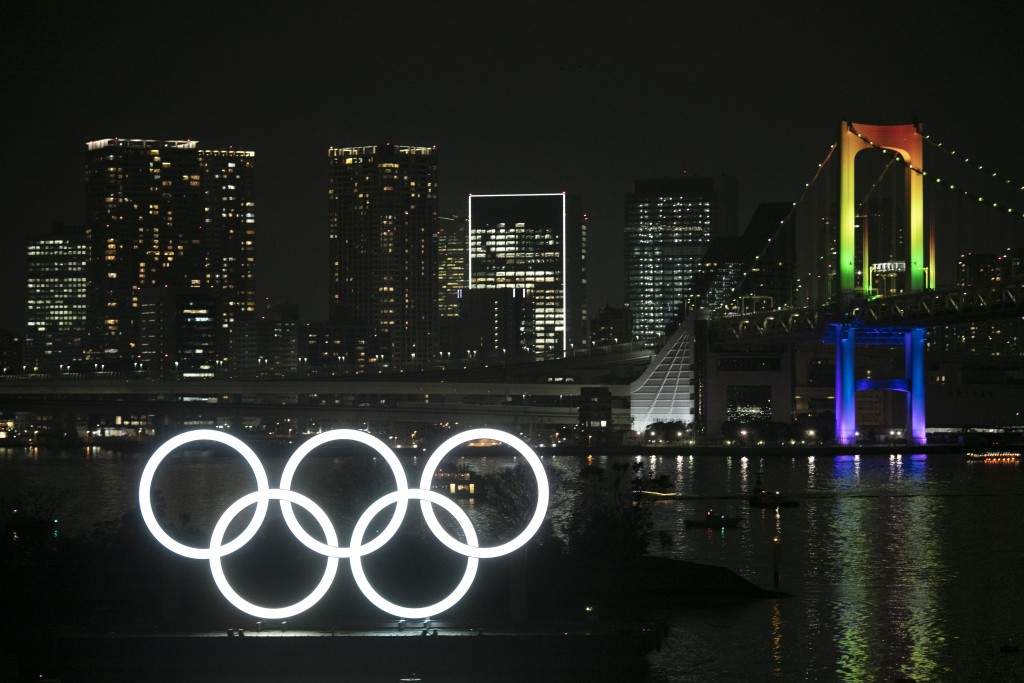The illuminated Olympic rings float in the water near the Rainbow Bridge during a ceremony held to celebrate the 6-months-to-go milestone for the Toky...