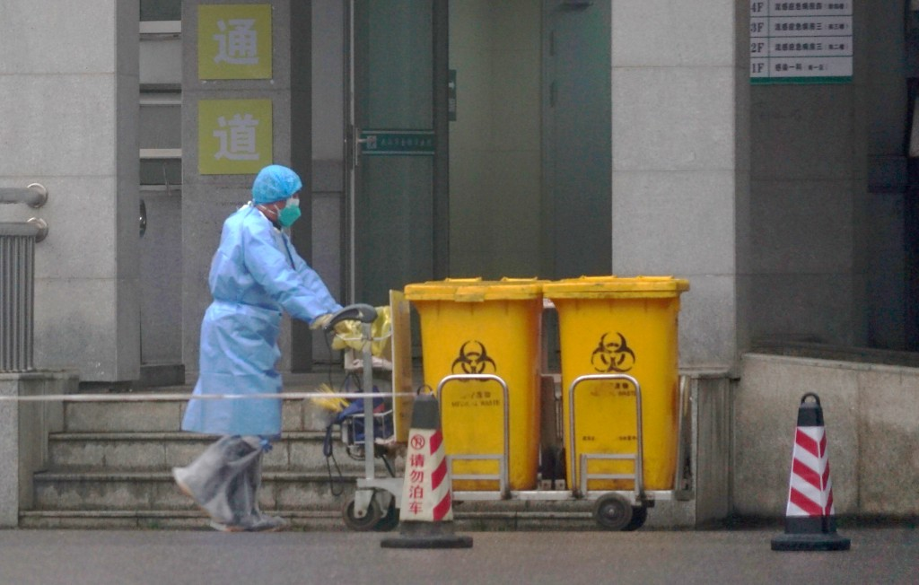 In this Wednesday, Jan. 22, 2020, file photo, staff move bio-waste containers past the entrance of the Wuhan Medical Treatment Center, where some infe...