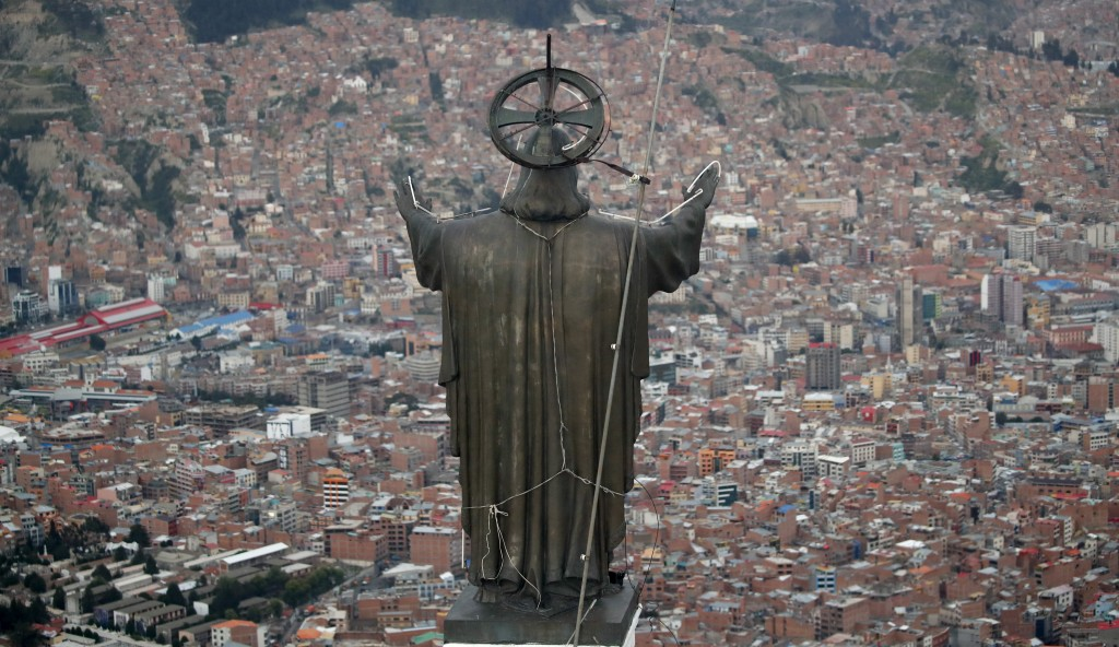 In this picture taken Tuesday, Jan. 7, 2020, a Christ statue overlooks El Alto, a city adjoining the capital city La Paz, Bolivia. Ancestral indigenou...