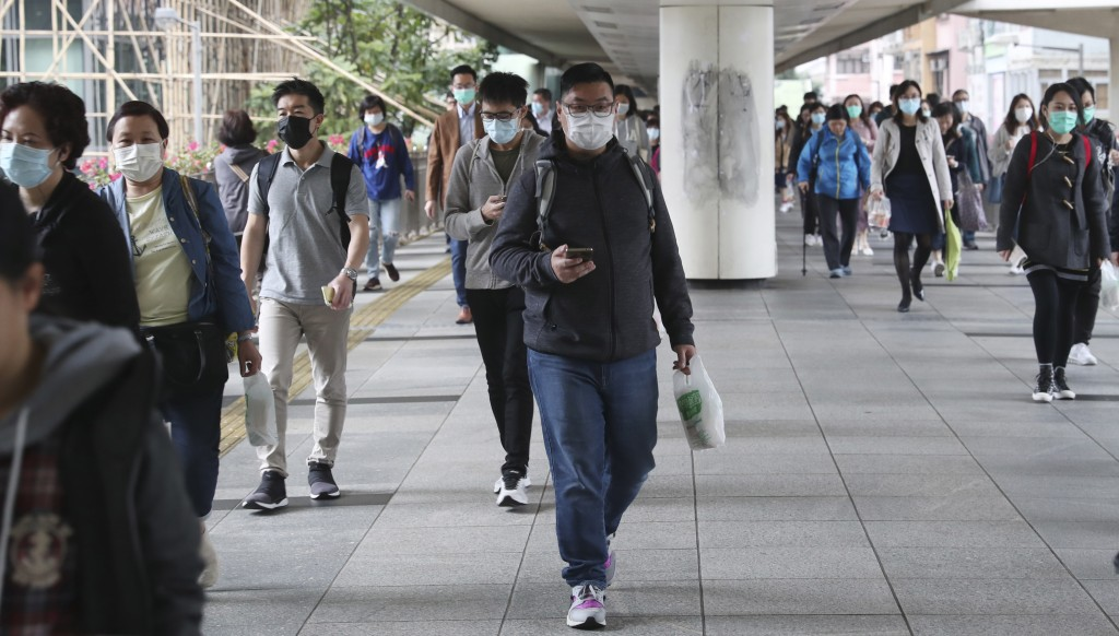 People wear protective face masks on a bridge in Hong Kong, Friday, Jan 24, 2020. China closed off a city of more than 11 million people Thursday, hal...