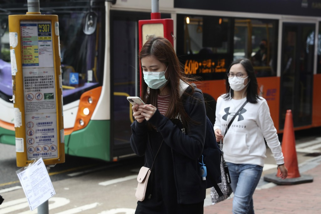 People wear protective face masks on a street in Hong Kong, Friday, Jan 24, 2020. China closed off a city of more than 11 million people Thursday, hal...