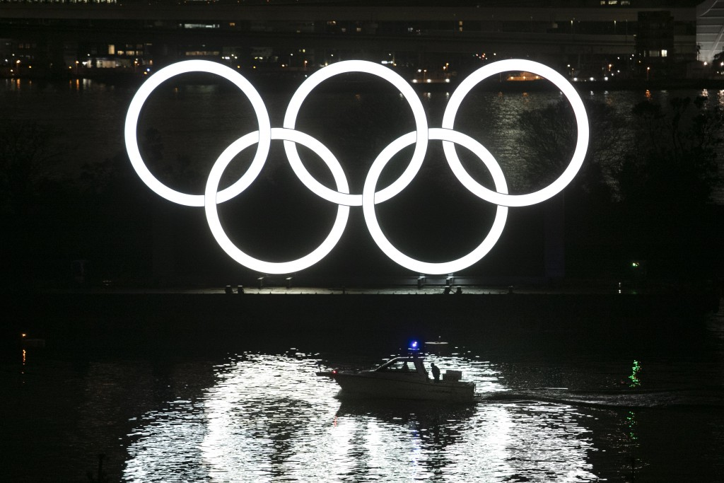 A small boat passes by the illuminated Olympic rings during a ceremony held to celebrate the 6-months-to-go milestone for the Tokyo 2020 Olympics Frid...