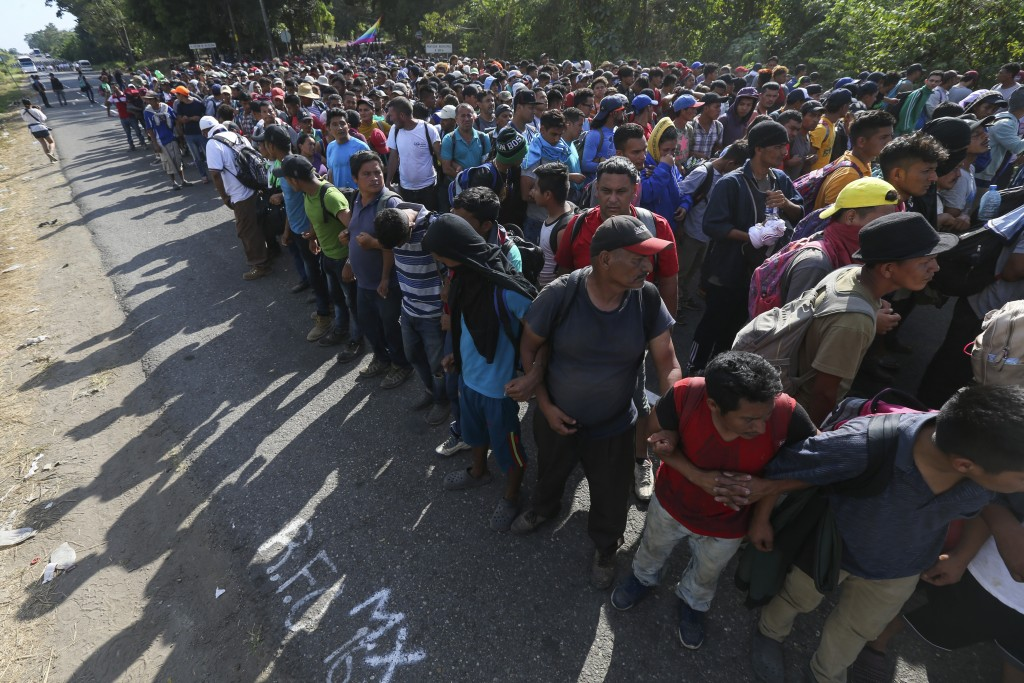 Migrants link arms on the highway leading to Tapachula, Mexico, Thursday Jan. 23, 2020, where they are blocked by National Guards. Hundreds of Central...