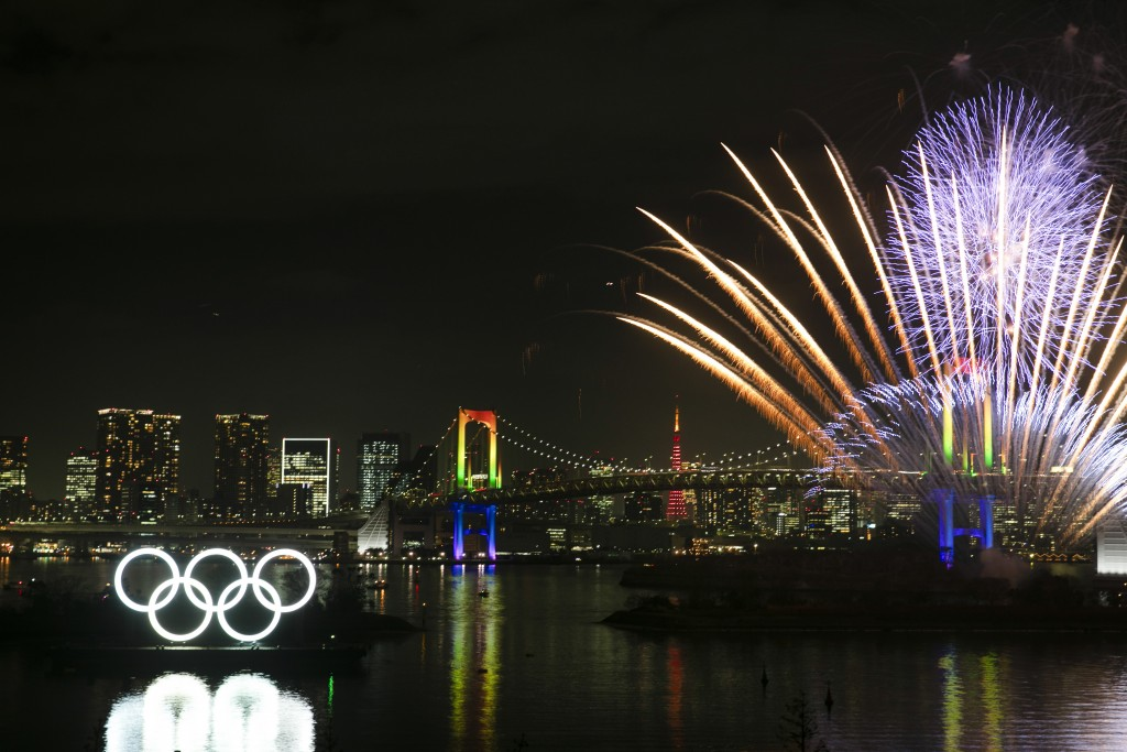 Fireworks explode near the illuminated Olympic rings during a ceremony held to celebrate the 6-months-to-go milestone for the Tokyo 2020 Olympics Frid...